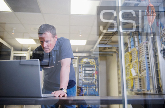 SSI Employee next to a laptop and networking station completing tasks of a business who is outsourcing IT in America